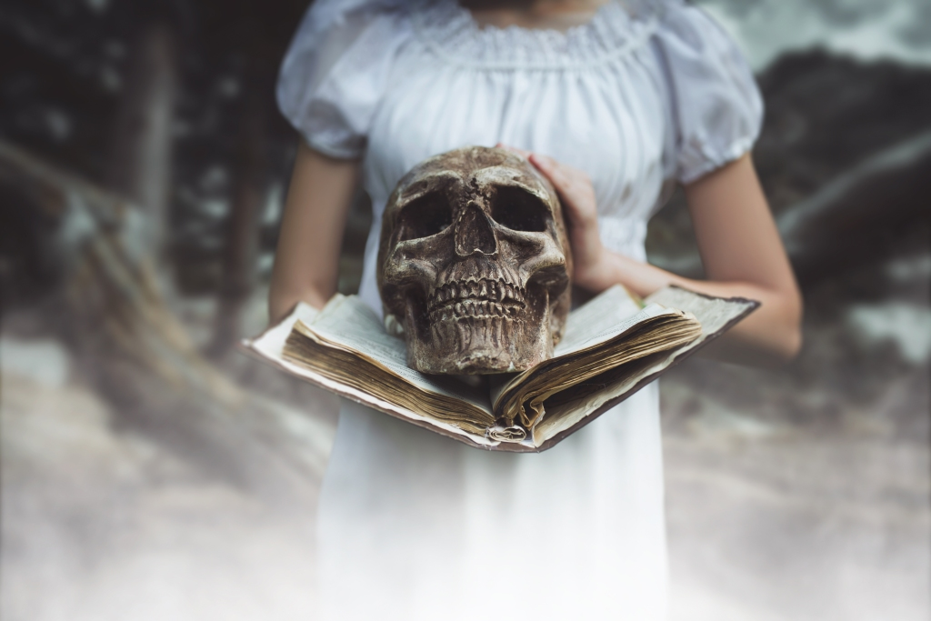 A girl in a soft white cotton dress holding an antique book in her hands with a yellowing, aged skull in the center resting on the book pages.