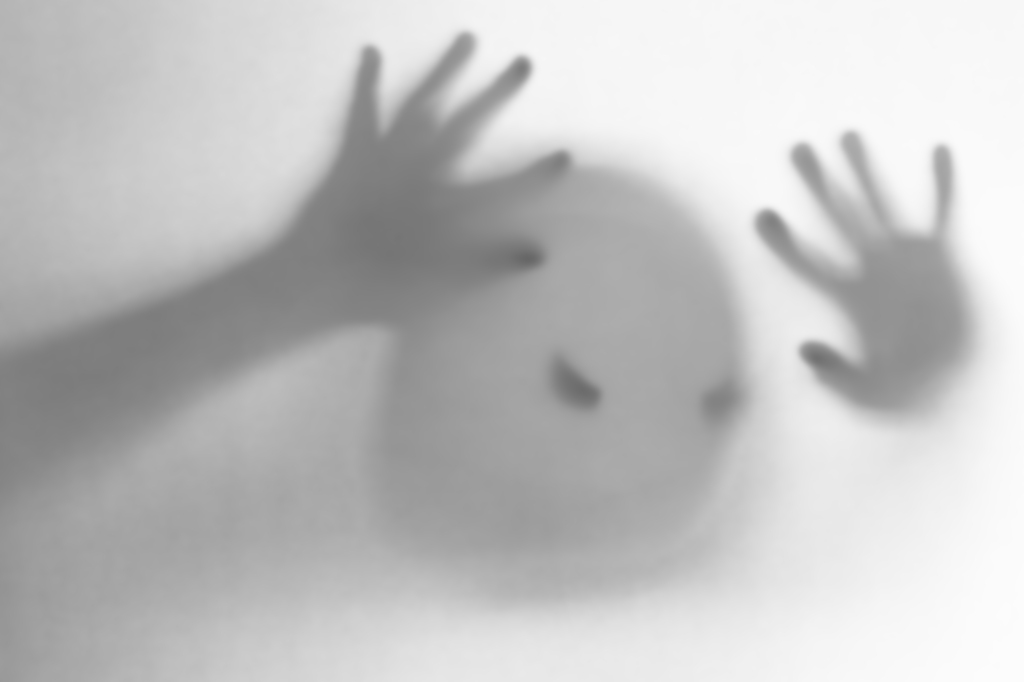 Halloween blurred background. A ghost resembling a pumpkin in color behind glass. Terrible and terrible nightmare. He knocks on the window