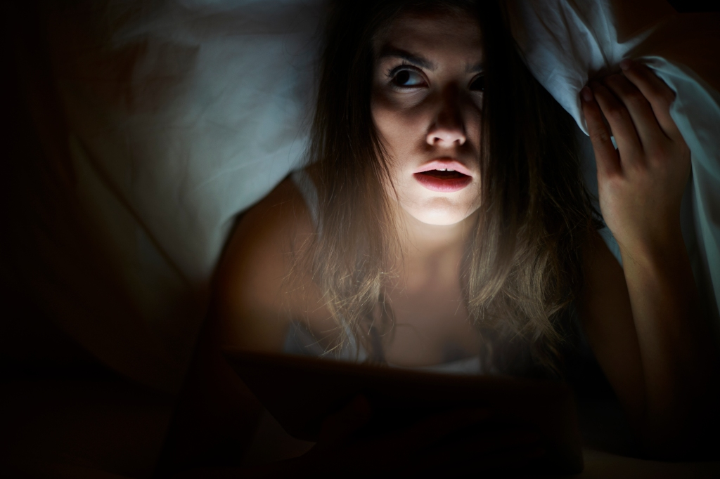 A girl is hiding under the covers peeking out, looking quite afraid, with her face illuminated by the screen of her tablet while she watches a movie