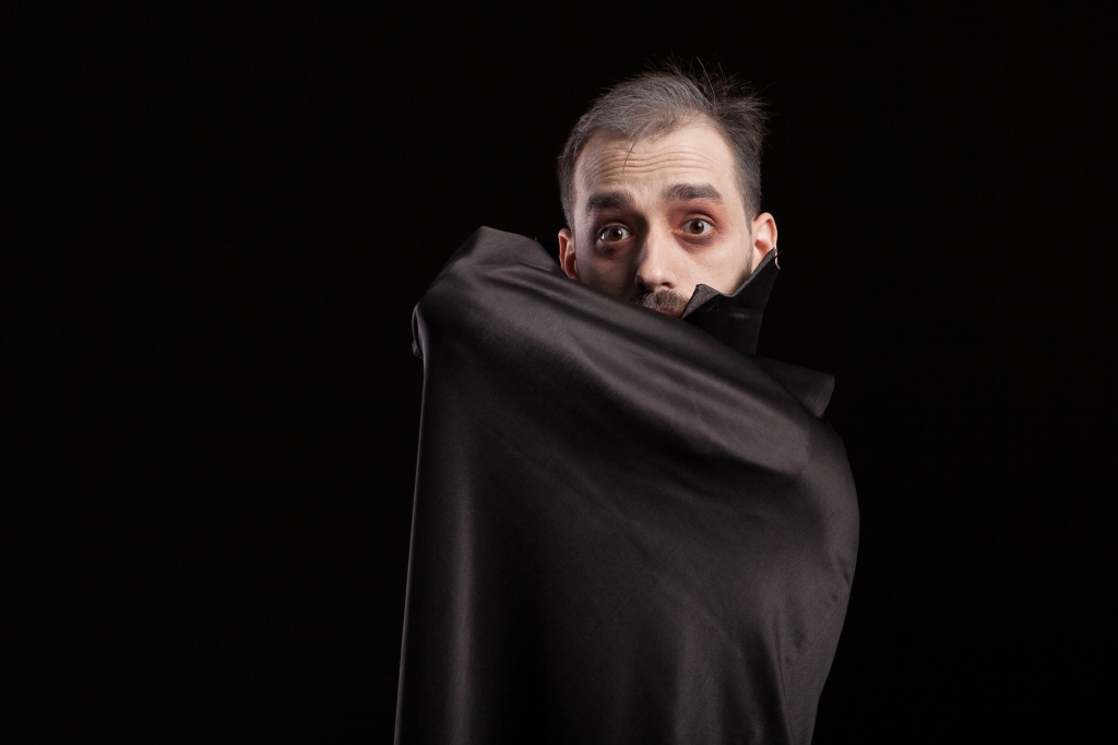 Man dressed up in dracula costume for halloween hiding behing his cape. Evil man in dracula costume. Spooky vampire.